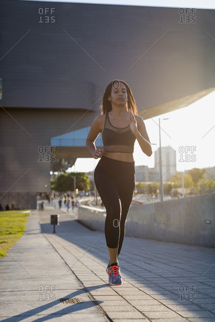 Young woman running in the city in sunlight
