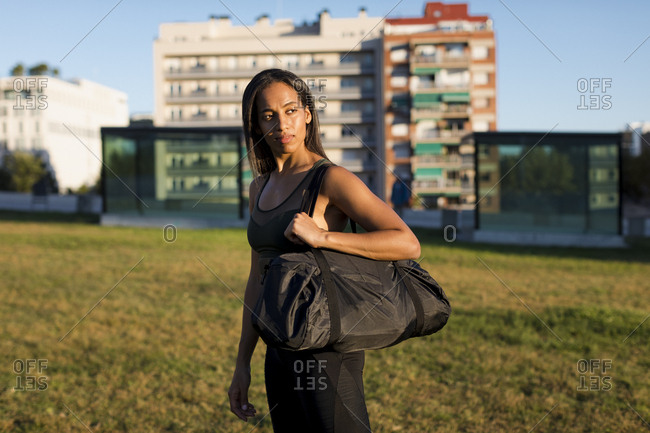 Sporty young woman with bag standing on meadow the city