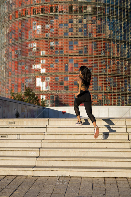Young woman running up stairs in the city