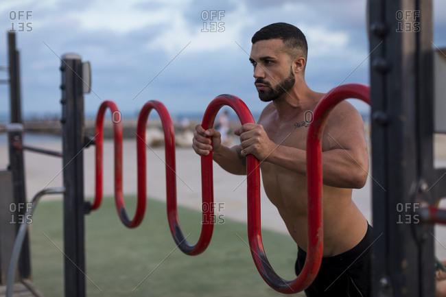 Barechested muscular man doing workout outdoors