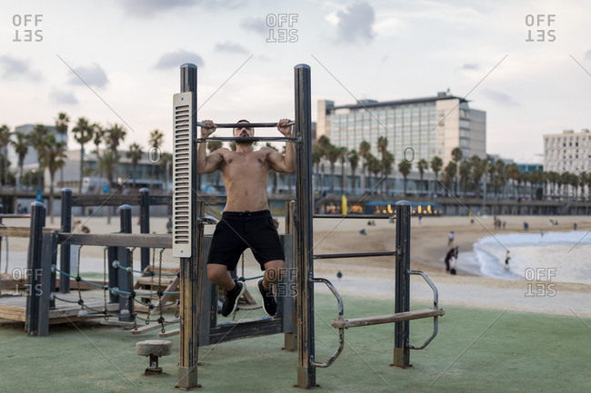 Barechested muscular man doing chin-ups on the beach