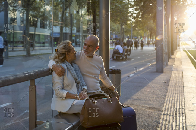 Spain- Barcelona- senior couple with baggage sitting at tram stop in the city at sunset