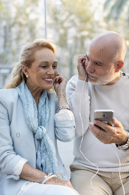 Spain- Barcelona- happy senior couple sharing smartphone with earbuds
