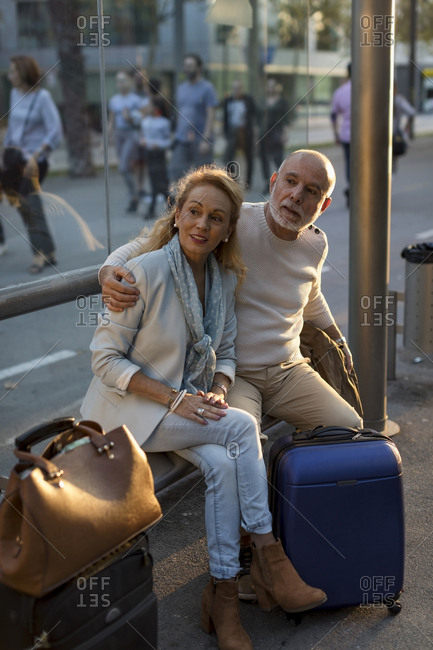 Spain- Barcelona- senior couple with baggage waiting at tram stop in the city