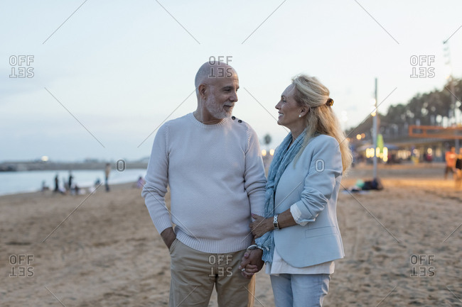 Spain- Barcelona- happy senior couple on the beach at dusk