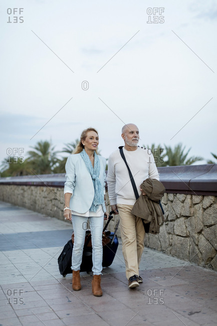 Spain- Barcelona- senior couple walking with baggage on the promenade