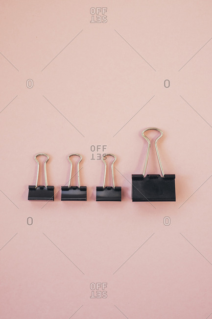 Black paper clips against pink background