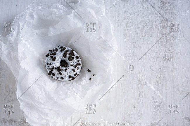 Doughnut with white icing and dark chocolate chips on white tissue paper