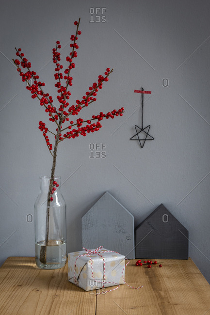 Wrapped present- decoration and   twig of holly in vase