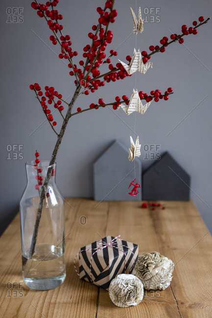 Wrapped present- paper decoration and twig of holly in vase