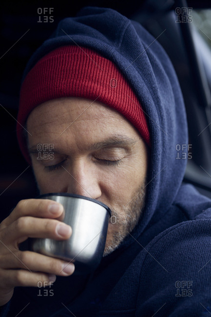 Portrait of mature man wearing red cap and blue hooded jacket drinking