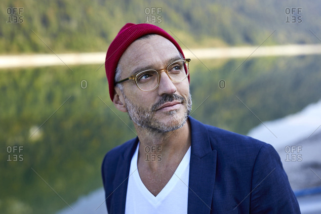 Portrait of bearded mature man wearing glasses and red cap in nature