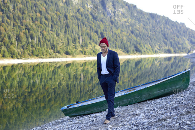 Mature man wearing red cap and blue suit walking barefoot at lakeshore