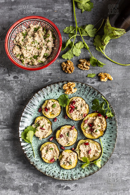 Baked aubergine slices spread with walnut creme garnished with pomegranate seeds