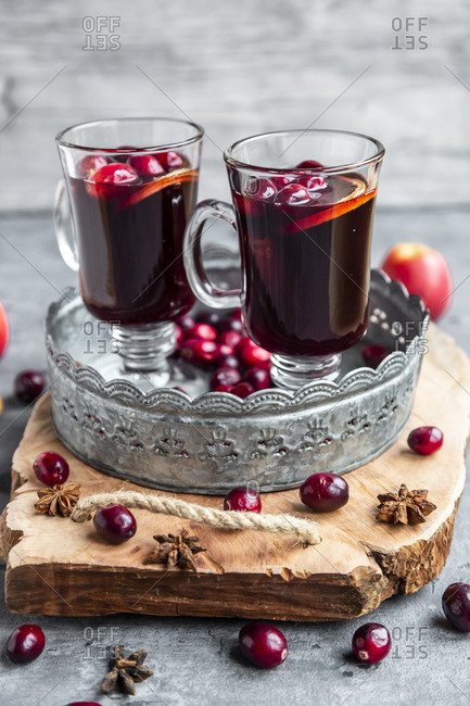 Two glasses of Mulled Wine with cranberries- orange slices and star anise on tray