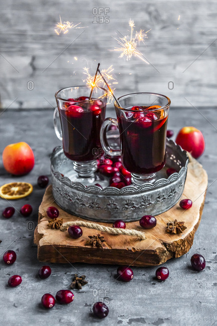 Two glasses of Mulled Wine with cranberries- orange slices and star anise with sparklers