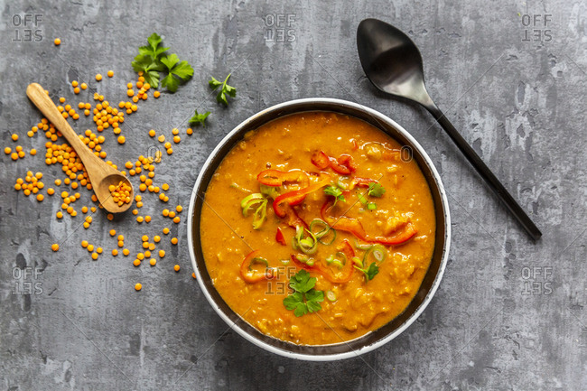 Soup bowl of garnished red lentil soup and ingredients