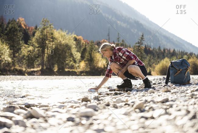 Austria- Alps- woman on a hiking trip having a break at a brook