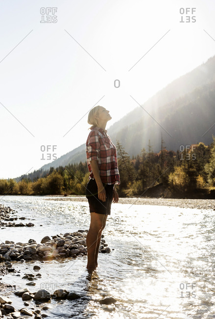 Austria- Alps- woman on a hiking trip standing in a brook