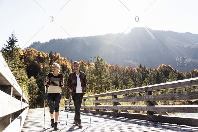 Austria- Alps- couple on a hiking trip crossing a bridge