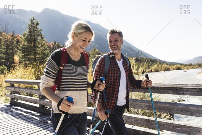 Austria- Alps- happy couple on a hiking trip crossing a bridge