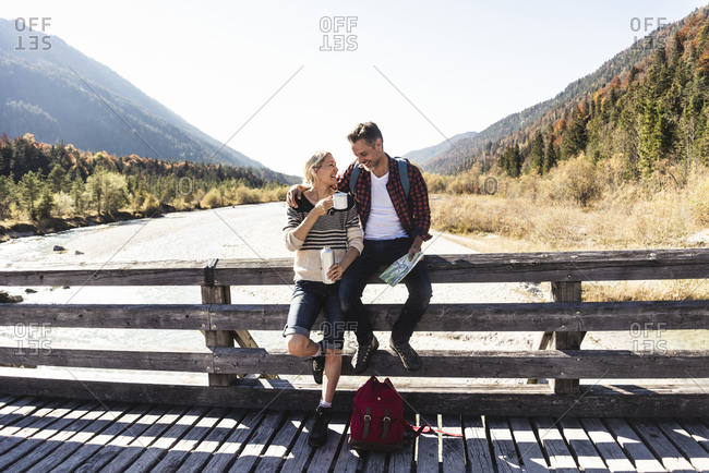 Austria- Alps- couple on a hiking trip having a break on a bridge