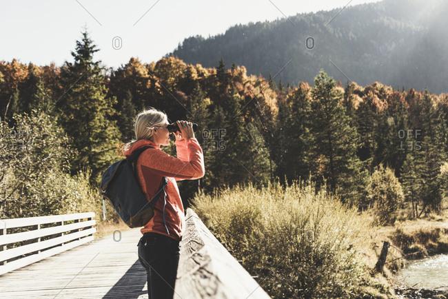 Austria- Alps- woman on a hiking trip looking through binoculars