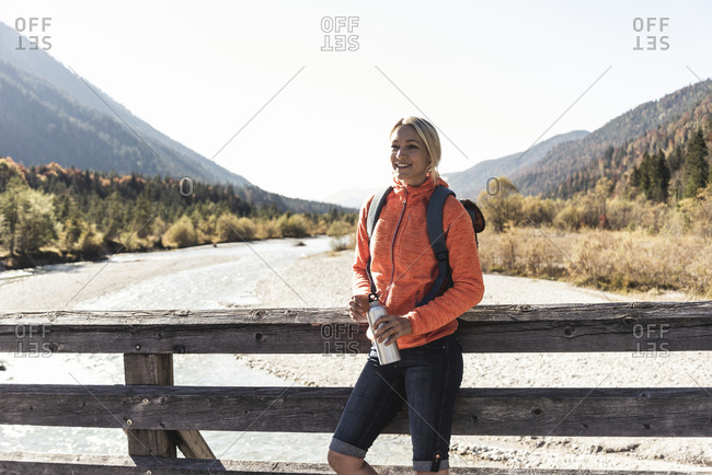Austria- Alps- woman on a hiking trip standing on a bridge with drinking bottle