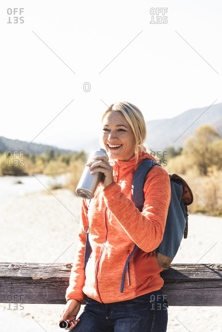 Austria- Alps- happy woman on a hiking trip drinking from bottle