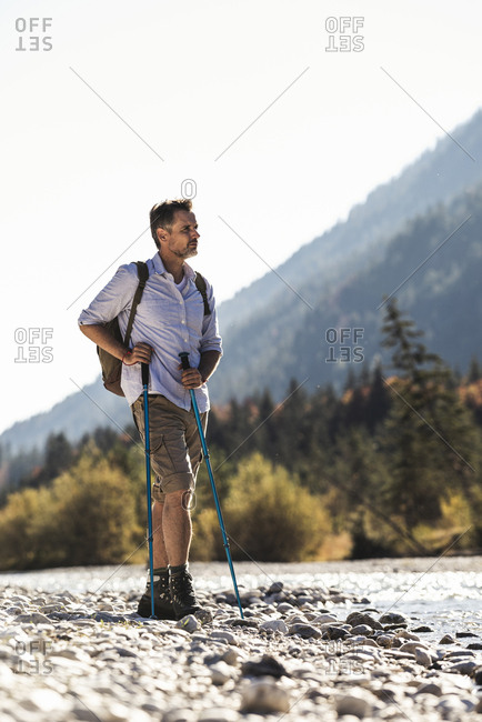Austria- Alps- man on a hiking trip standing on pebbles at a brook