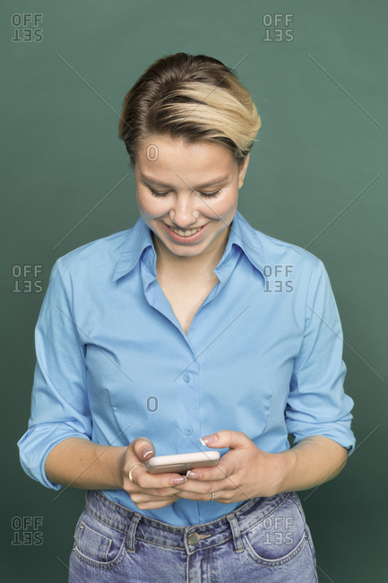 Smiling young woman with dyed hair using smartphone in front of green background