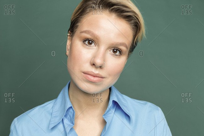 Portrait of young woman with nose piercing in front of green background
