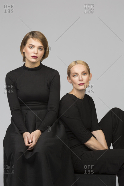 Studio portrait of mother and adult daughter sitting down