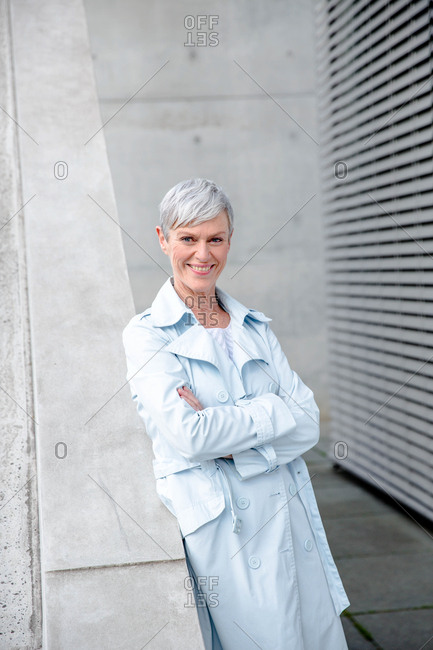 Portrait of content mature businesswoman leaning against wall wearing light blue trenchcoat