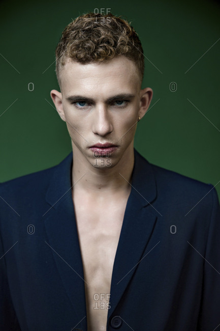 Portrait of self-confident half-naked young man in studio