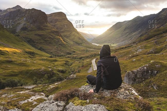 UK- Scotland- Man looking at view with the Three Sisters of Glencoe mountains on the left and the A82 road in the middle of the valley
