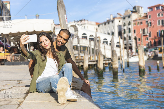 Italy- Venice- couple relaxing and taking a selfie with Rialto bridge in background