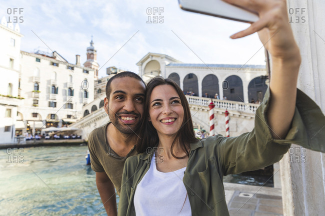 Italy- Venice- couple enjoying the city and taking a selfie with Rialto bridge in background