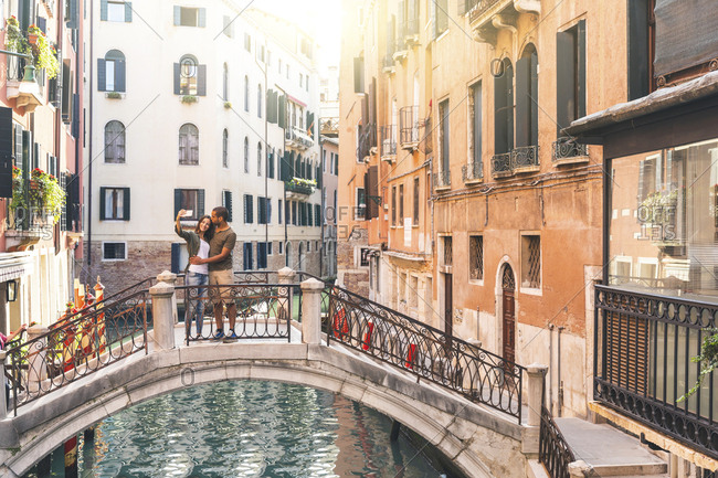 Italy- Venice- young couple standing on a small bridge taking a selfie