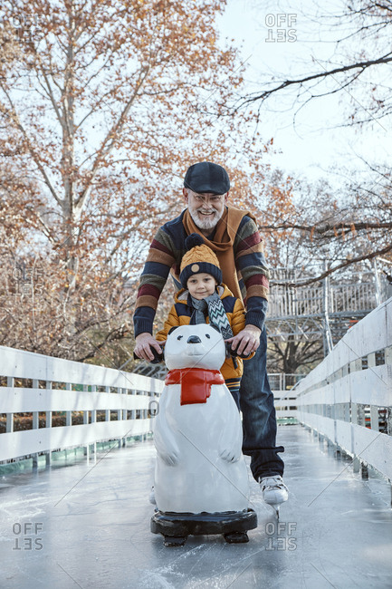 Grandfather and grandson on the ice rink- ice skating- using ice bear figure as prop