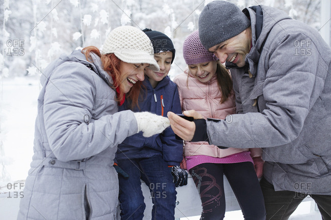 Family with two kids on the ice rink- looking at selfies on their smartphone