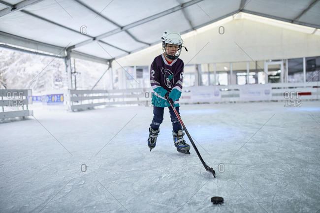 Boy playing ice hockey on the ice rink