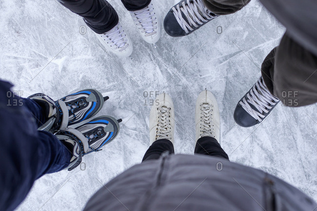 Family with two kids standing on the ice rink- close up of shoes