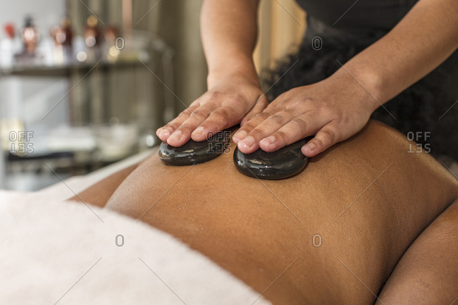 Woman receiving a hot stone massage in a spa