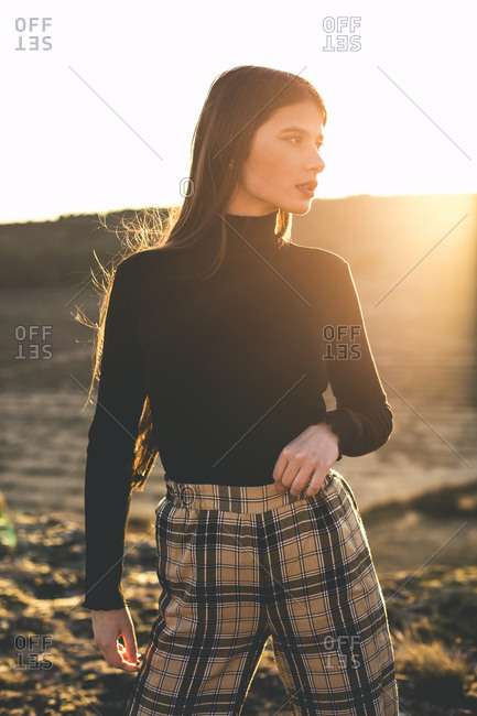 Portrait of fashionable teenage girl wearing black pullover and checked trousers at sunset