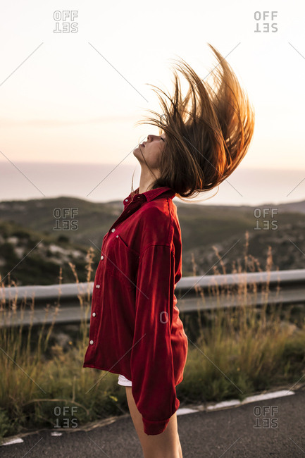 Young woman tossing her hair on country road at sunset