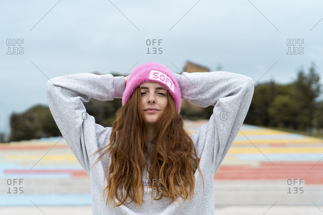 Portrait of smiling redheaded woman wearing pink cap with the word 'soft'