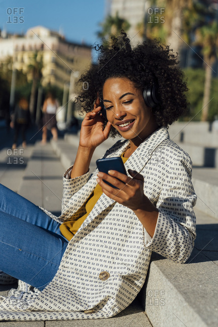 Beautiful woman sitting on stairs in the city- using smartphone- listening music with headphones