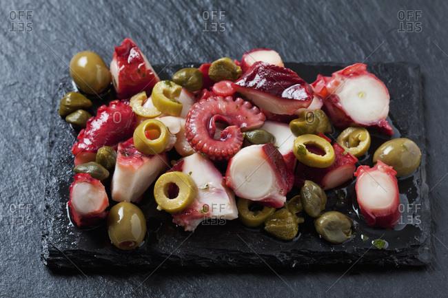 Octopus salad on black slate slab