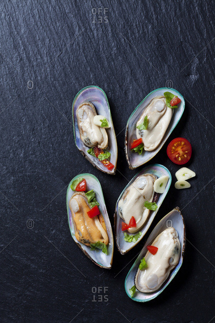 Green mussels with tomatoes- capsicum and garlic- on black slate slab